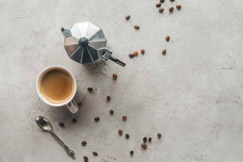 Flat lay of moka pot and coffee cup