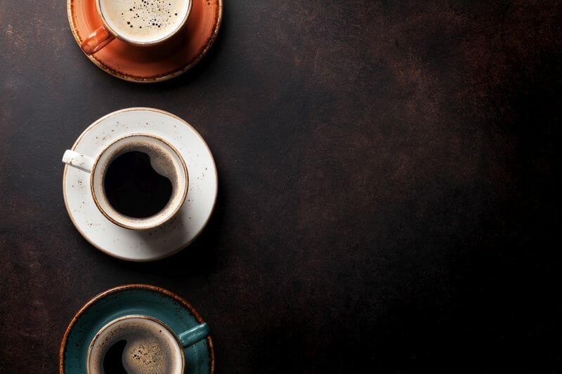 3 coffee cups on dark background