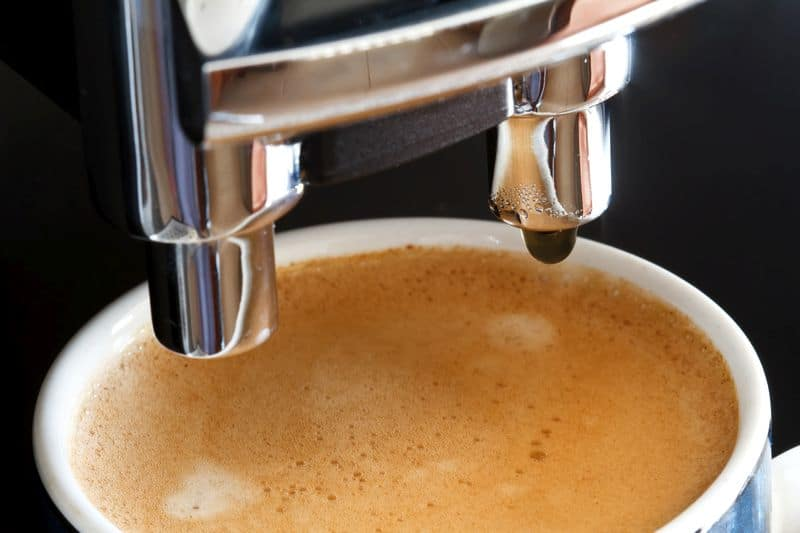 Close up of espresso in cup next to fully automatic espresso machine