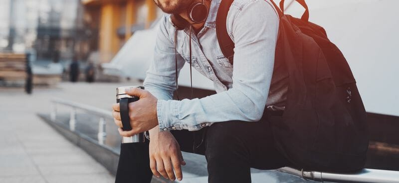 Guy with backpack holding coffee thermo mug in hands
