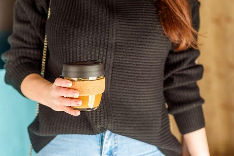 businesswoman holding reusable takeaway glass coffee cup - zero waste