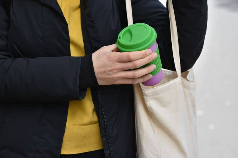 Woman holding reusable coffee cup putting into a bag outdoors. Zero waste. Sustainable lifestyle