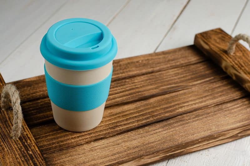 eco friendly bamboo coffee cup on wooden tray