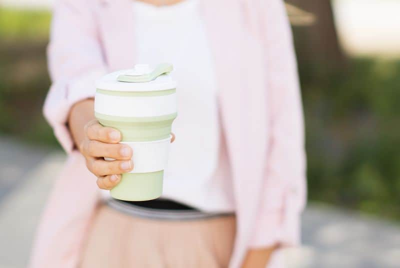 Female hands hold reusable coffee mug. Zero waste concept. Sustainable lifestyle.