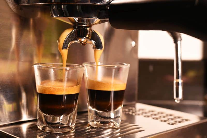 Close up of portafilter extracting espresso into glasses