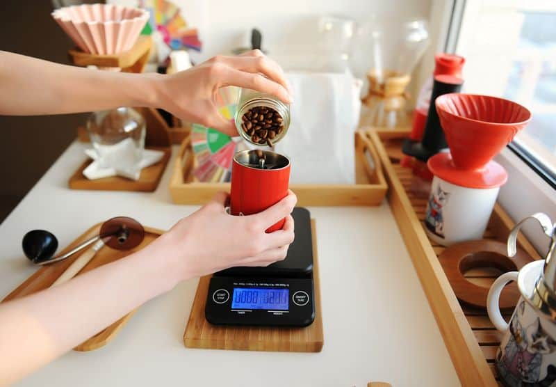 Pouring coffee beans into red manual coffee grinder on electronic scale