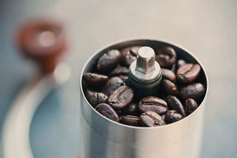 Coffee beans in a hand grinder closeup