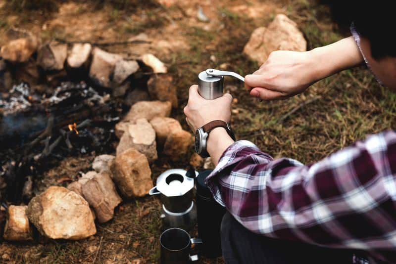 Coffee bean grinder manual process next to campfire