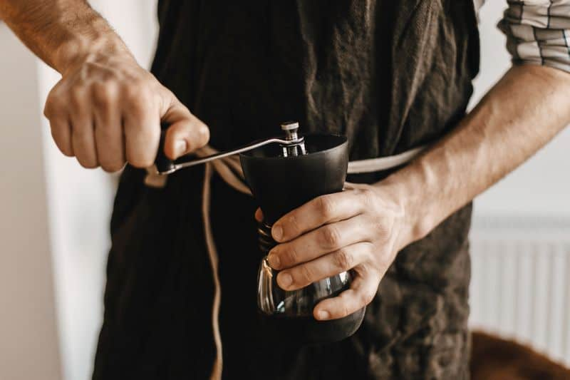 Hands holding coffee grinder hand crank.