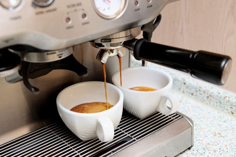 espresso machine extracting espresso into two white coffee cups