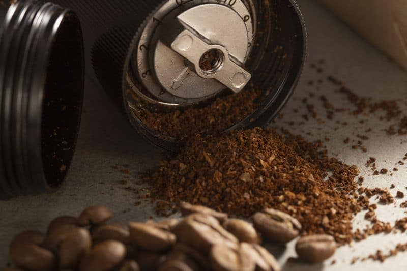 Inside a stepped manual coffee grinder with ground beans