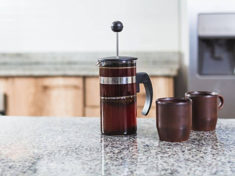 Glass coffee press brewing coffee on kitchen bench with two coffee mugs