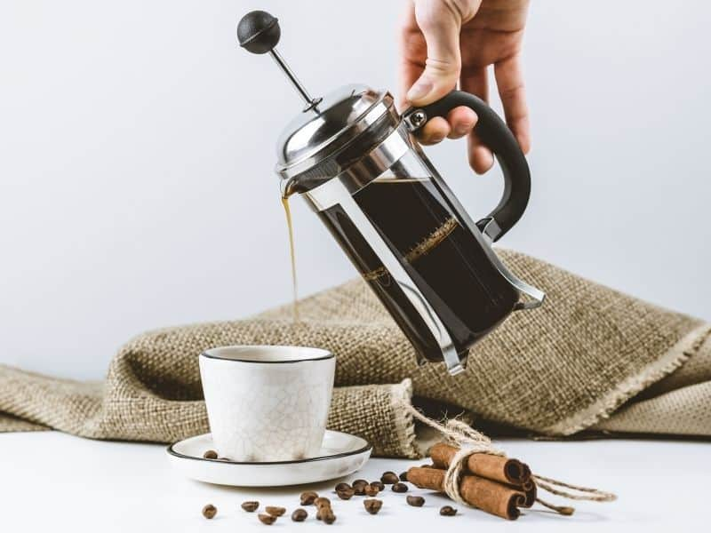 French press coffee maker pouring coffee into cup