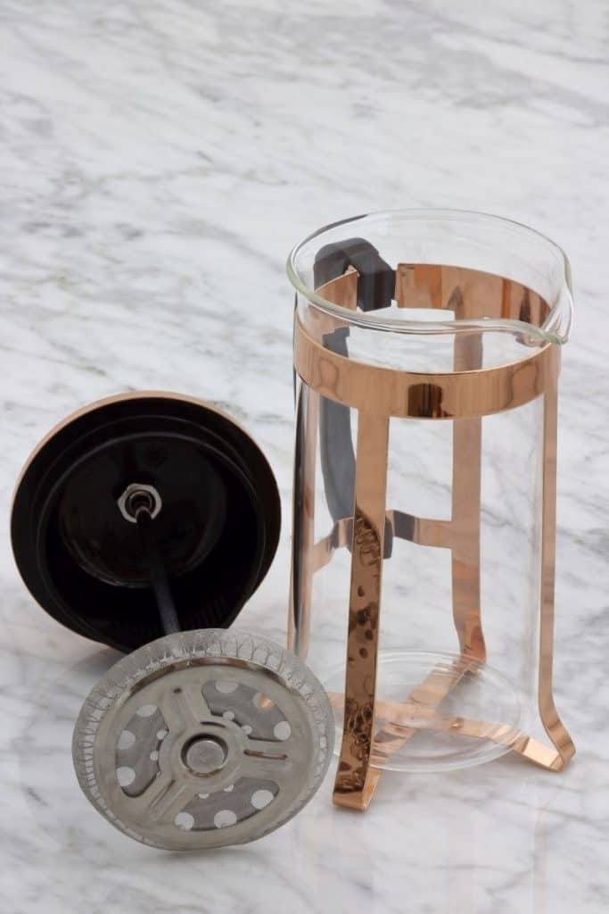 Empty glass french press coffee maker with stainless steel filter and plunger.