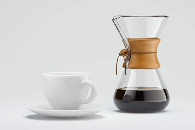freshly prepared black coffee in chemex pour over coffee maker near white coffee cup