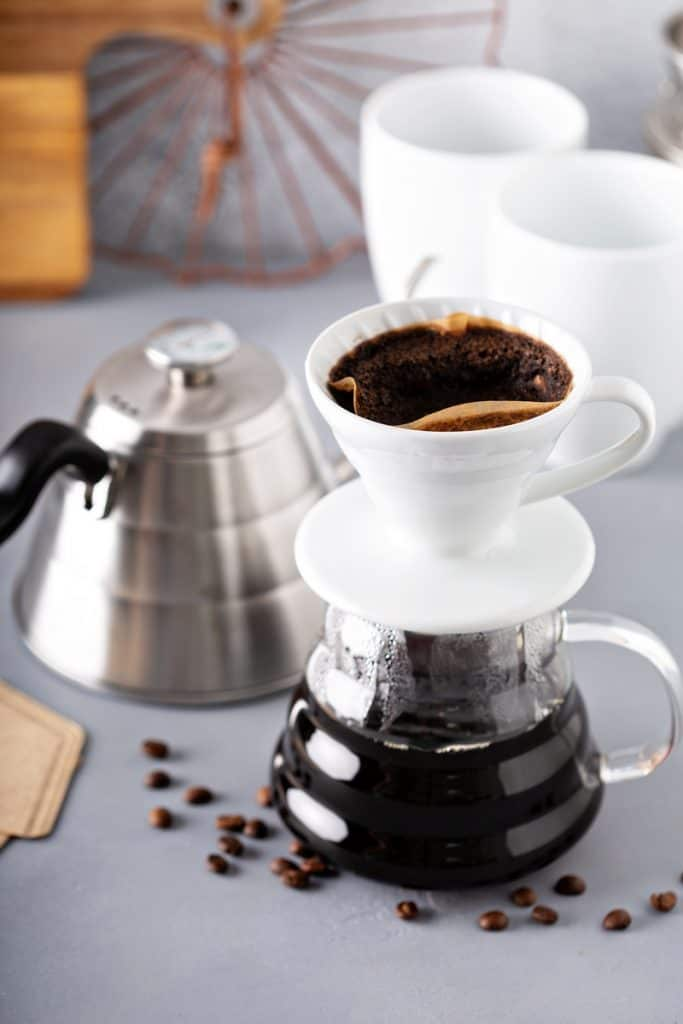 Pour over coffee being made with a gooseneck kettle and glass carafe