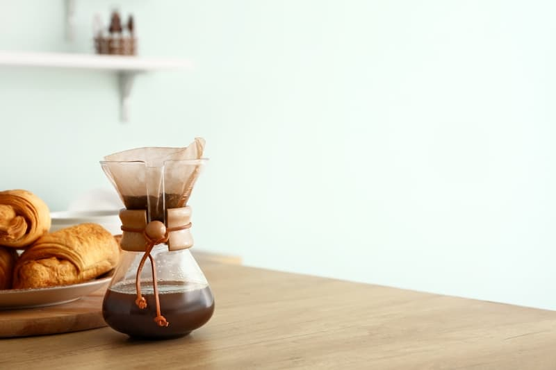 Chemex pour over coffee maker with hot coffee on wooden table.