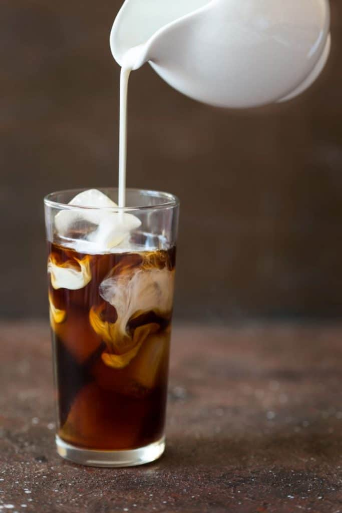 Iced cold brew coffee in a tall glass with cream poured over.
