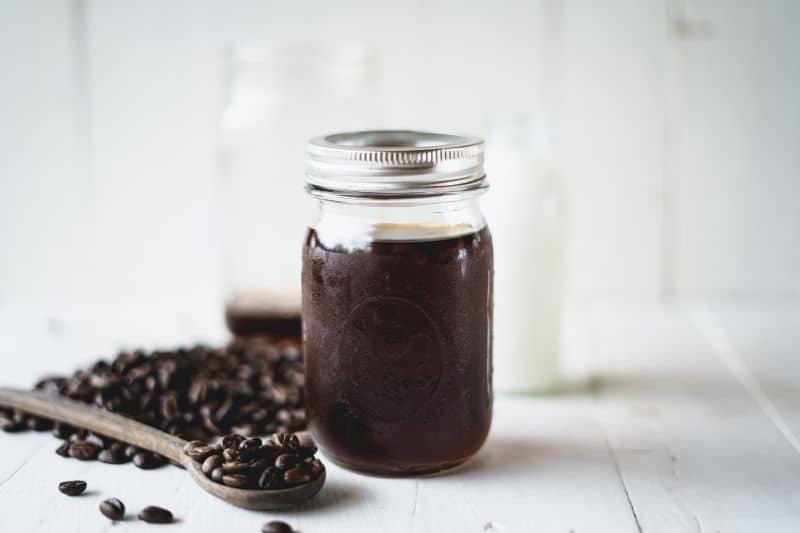 Mason jar cold brew coffee with coffee beans.